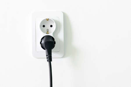 cut out device: European white electrical outlet socket and black cable pluged in isolated on white wall