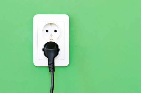 grounded plug: European white electrical outlet socket and black cable pluged in isolated on green wall