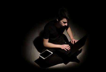 though: Teenager young man working on laptop and tablet isolated on black background