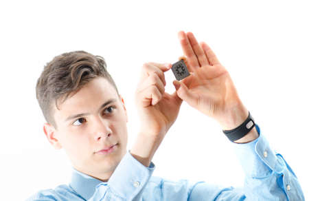 micro chip: Teenager man concentrated looking at a micro chip isolated on white