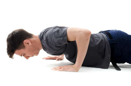Teenager making push ups in jeans and t-shirt isolated on white