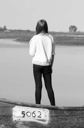 back posing: Teenager girl back posing on a wooden boat near a lake black and white Stock Photo