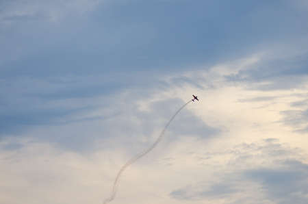 acrobatic: Acrobatic plane aircraft with smoke behind on blue sky