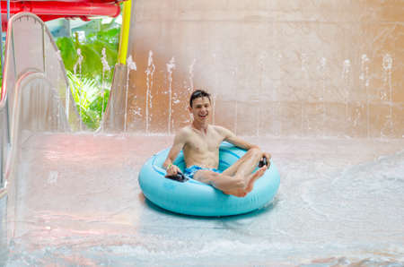pool preteen: Teen boy on a inflatable tube going down a water slide