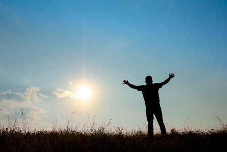 manos levantadas al cielo: Silueta de hombre culto con las manos levantadas hacia el cielo en el concepto de naturaleza de alabanza, adoración, religión