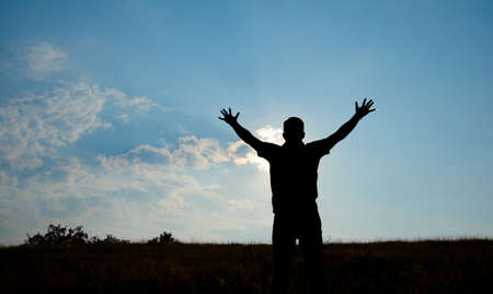 Silhouette of man worship with hands raised to the sky in nature concept of religion, prayer, worship