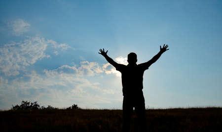 manos levantadas al cielo: Silueta de hombre culto con las manos levantadas hacia el cielo en concepto de la naturaleza de la religi�n, la oraci�n, el culto Foto de archivo