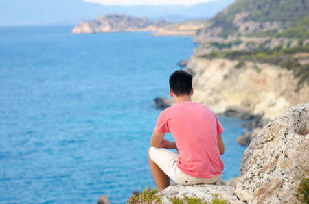 Teenager man sit on rock on beach near deep blue sea at Ionian Sea