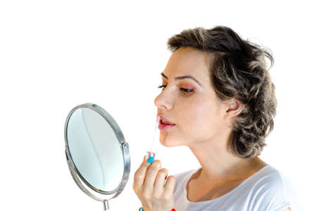 in vain: Portrait of woman apply lipstick make-up look in small mirror isolated on white Stock Photo