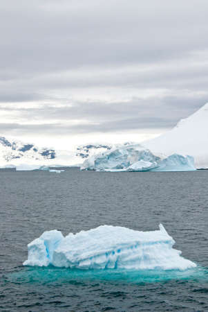 tabular: Iceberg Drifting In The Ocean of Antarctica In A Cloudy Day Stock Photo