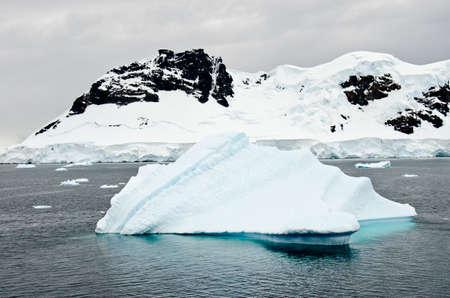 calving: Antarctica - Non-Tabular Iceberg Drifting In The Ocean - Antarctica In A Cloudy Day - Global Warming