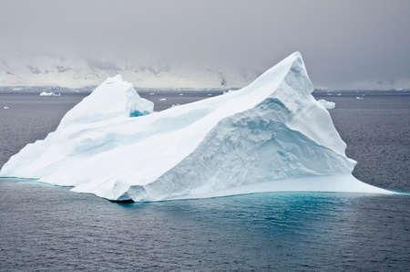 tabular: Antarctica - Non-Tabular Iceberg Drifting In The Ocean - Antarctica In A Cloudy Day