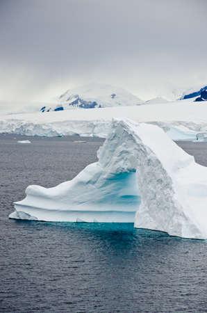 tabular: Antarctica - Non-Tabular Iceberg - Pinnacle Shaped Iceberg Drifting In The Ocean - Antarctica In A Cloudy Day Stock Photo