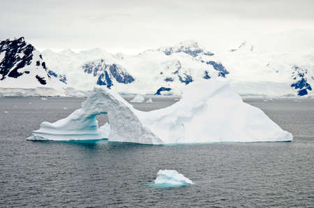 pinnacle: Antarctica - Non-Tabular Iceberg - Pinnacle Shaped Iceberg Drifting In The Ocean - Antarctica In A Cloudy Day Stock Photo