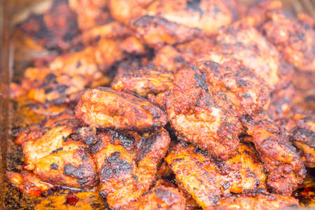 Spicy Grilled Jerk Chicken on the barbecue - style of cooking native to Jamaica - Food Street Market Stock Photo