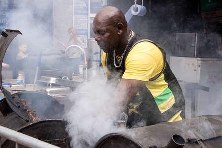 Jamaican chef cooking jerk chicken - Food Street Market Reading, UK - June2, 2018 Editorial