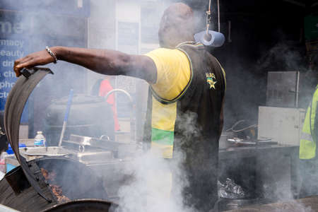 Jamaican chef cooking jerk chicken - Food Street Market Reading, UK - June2, 2018