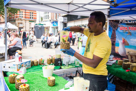 African ethnic preparing pina colada in pineapple on street - Food Street Market Reading, United Kingdom - June 2, 2018