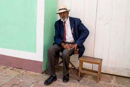 Elderly man with hat and beard smoking cigar in Trinidad, Cuba. Photo taken on 3rd of November, 2019
