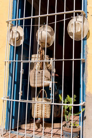 Hats on display in street window, behind iron bars in Trinidad, Cuba, Central America. Photo taken on 3rd of November, 2019 Imagens