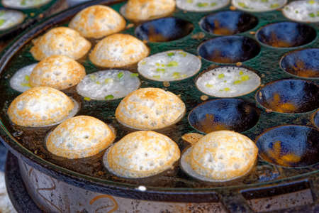 Traditional thai street food dessert, Kanom Krok or coconut rice pancakes. Close-up street food background from Thailand Stockfoto