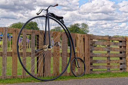 Antique vintage bicycle parked on a wooden fence - United Kingdom Standard-Bild