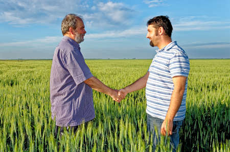 Two farmers shake hands against the background of a wheat field - Conclusion of a contract - Done Deal - Calarasi, Romania - 28th of June 2011