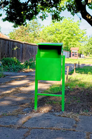 Street green painted waste bin in city park