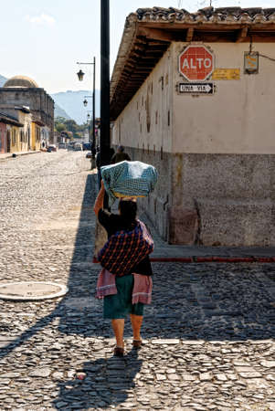 Woman carries a basket on her head as she goes to the market in Antigua Guatemala, Sacatepequez, Guatemala, Central America - 24th of March 2011