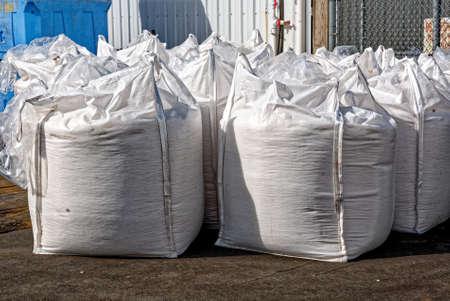 Bags of road salt - white salt sacks rows stacked to prevent ice roads asphalt Foto de archivo