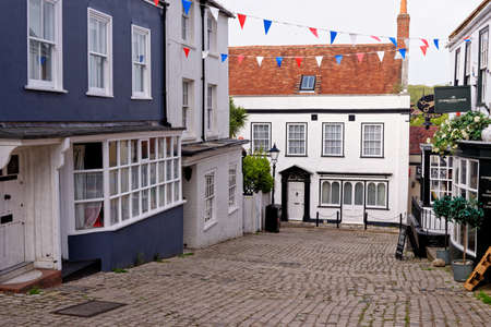 Lymington Hampshire - colorful rendered walls and bay windows on shopfronts along hilly cobbled Quay Hill street in England UK - 20th of May 2021