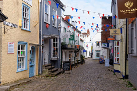 Lymington Hampshire - colorful rendered walls and bay windows on shopfronts along hilly cobbled Quay Street in England UK - 20th of May 2021