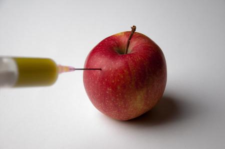 apple gmo: Apple GMO syringe Injection into red apple Stock Photo