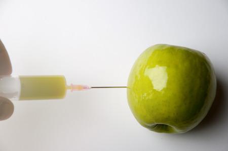 apple gmo: GMO apple with syringe on the white