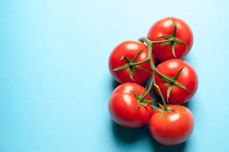heathy diet: Five fresh tomatoes on a blue background from above with text space
