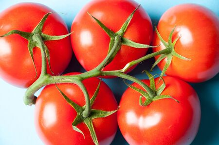 heathy diet: Five fresh tomatoes on a blue background from above Stock Photo