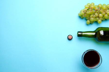 winy: Glass, bottle of wine, green grapes on a blue background