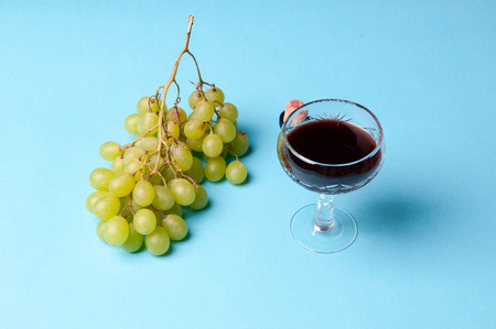 winy: Glass of wine and green grapes, isolated on blue