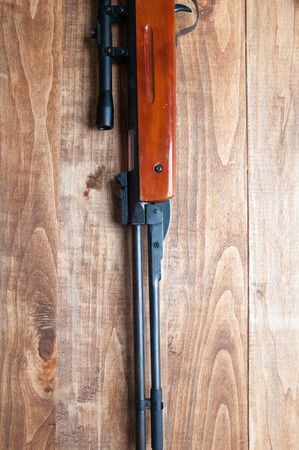 backgound: Air rifle isolated on wooden backgound