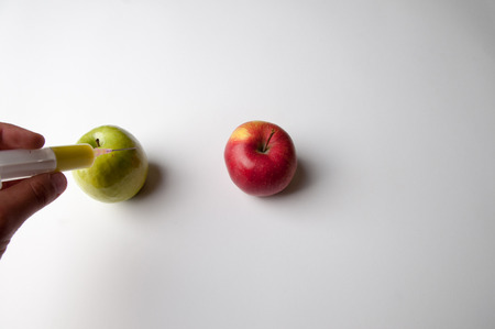 Green and red apple with syringe. GMO Stock Photo