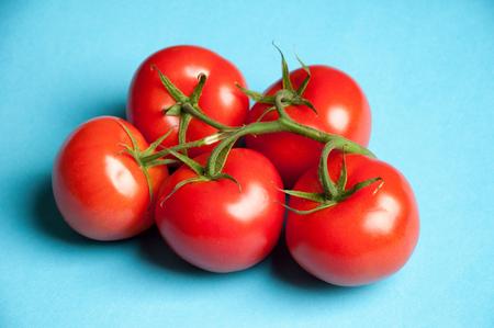 heathy: Five fresh tomatoes on a blue background