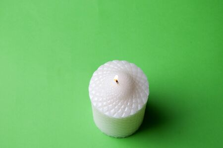 White candle isolated on green background