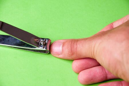 Nail clippers isolated on green background. Stock Photo