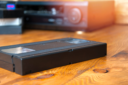 videocassette: Equipo para la reproducci�n de cintas de VHS en una mesa de madera.