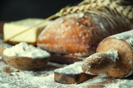 Bread and additions on a wooden table.