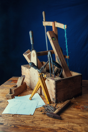 carpenter's sawdust: Equipment carpenter on a wooden desk with plans.