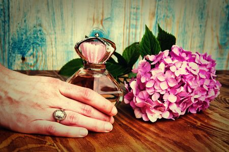 Hand holding a perfume and hydrangea wooden background