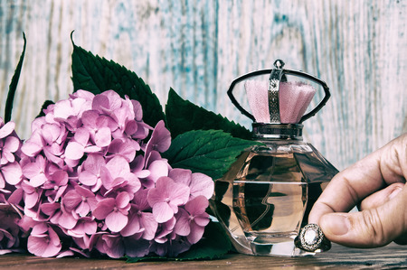 Perfumes and hydrangea wooden background Stock Photo