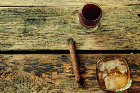 Lit cigar, wine and whiskey on a wooden background from above.