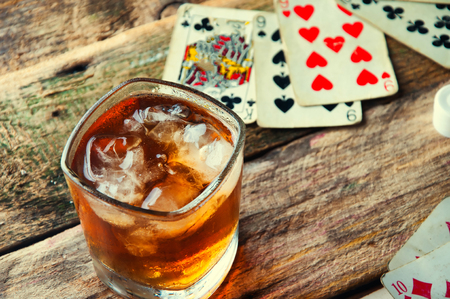 Whiskey, cigar and cards on a wooden background. Banque d'images